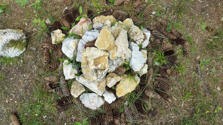 Ein Kranz der mit Tannenzapfen und Steinen gemacht wurde. Die Tannenzapfen bilden den Rand und die Steine sind in der Mitte übereinandergestapelt.