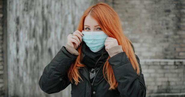Frau, die ihren Mund-Nasen-Schutz aufzieht
